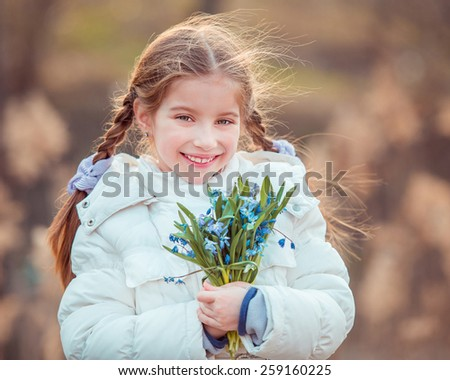 happy little girl smiling and holding a bouquet of a blue snowdrops - stock photo