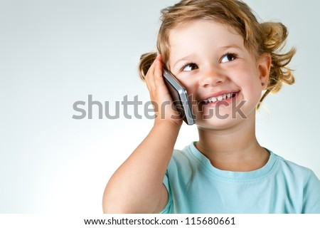 Happy little girl speaking by cell phone against light gray-blue background with copy space - stock photo
