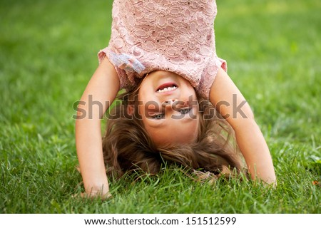 Happy little girl standing on her head on the grass in the park. Childhood concept. Summer holiday. - stock photo