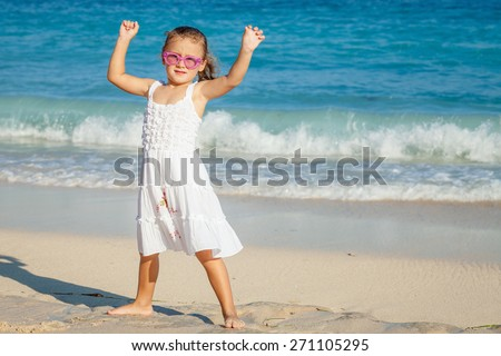 Happy Little girl  standing on the beach at the day time