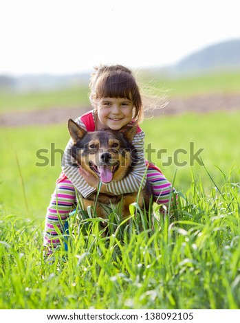 Happy little girl straddled the dog on the meadow - stock photo