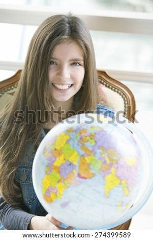 Happy little girl studying with earth globe - stock photo
