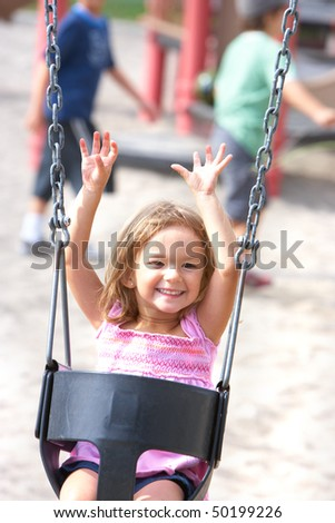 Happy  little girl swinging in the park - stock photo