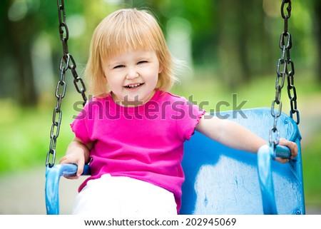 Happy little girl swinging on playground area - stock photo