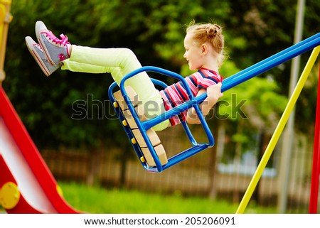 Happy little girl swinging on playground area - stock photo