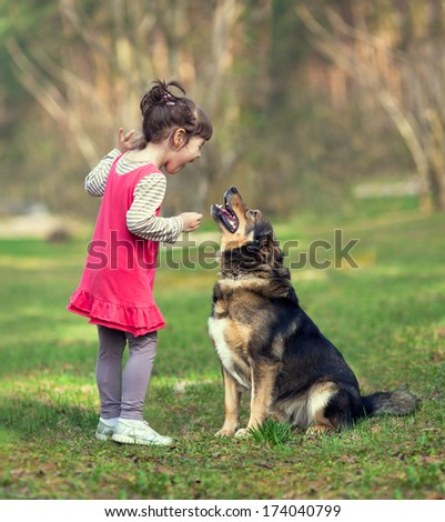 Happy little girl talking to dog - stock photo