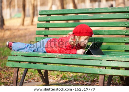 Happy little girl using tablet outdoors. Computer generation concept. - stock photo