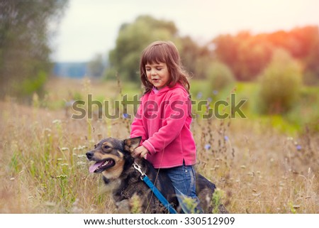 Happy little girl walking with dog on the meadow