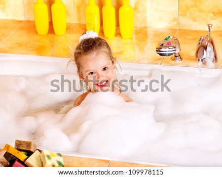 Happy little girl washing in bubble bath . - stock photo