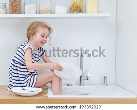 Happy little girl washing the dishes in the kitchen. - stock photo