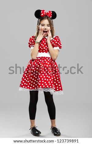 Happy little girl wearing a carnival costume, against a gray background - stock photo
