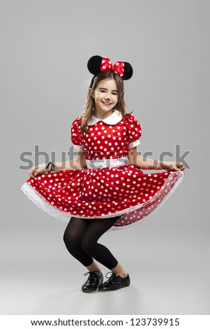 Happy little girl wearing a carnival costume, against a gray background