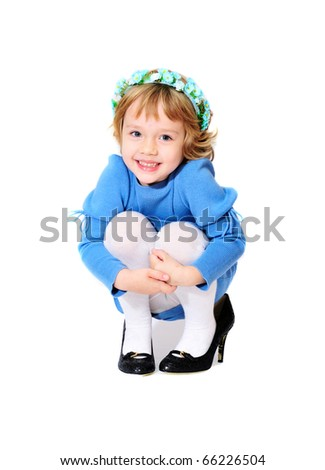happy little girl wearing mother's shoes - stock photo