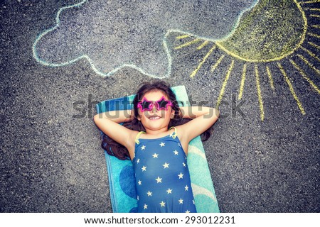 Happy little girl wearing swimsuit and stylish sunglasses lying down on the asphalt near picture of the sun comes out from behind the clouds, cute baby needs of summer holidays - stock photo