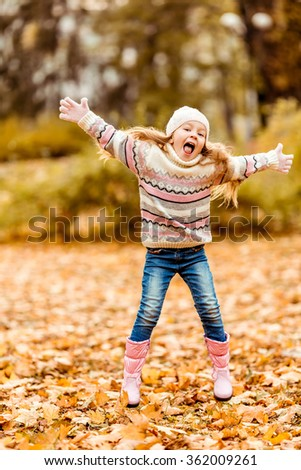 Happy little girl while walking in the autumn park. - stock photo