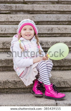 happy little girl with a balloon sitting on the steps - stock photo