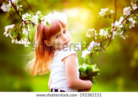 Happy little girl with a bouquet of lilies of the valley having fun in the blooming spring garden - stock photo