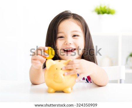 happy little girl with a piggy bank - stock photo