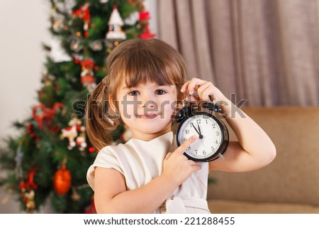 Happy little girl with an alarm clock in his hands waiting for Christmas - stock photo