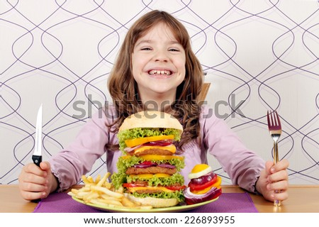 happy little girl with big hamburger on table - stock photo