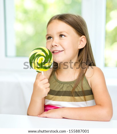 Happy little girl with big lollipop - stock photo