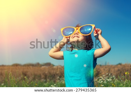 Happy little girl with big sunglasses walking in the meadow and looking at the sun - stock photo