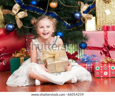 Happy little girl with Christmas gifts - stock photo