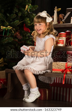 Happy little girl with Christmas gifts sitting near Christmas tree - stock photo