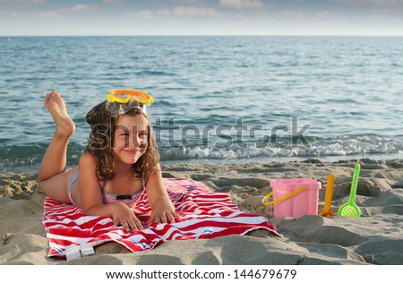 happy little girl with diving mask lying on beach - stock photo