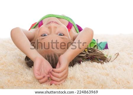 Happy little girl with dreadlocks lays on her back. Girl six years. - stock photo