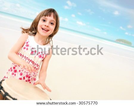 Happy little girl with drum on the beach - stock photo