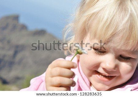 Happy little girl with eyes closed, smelling flowers in his hand against the blue sky - stock photo