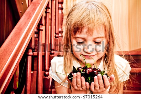 Happy little girl with fake cherry berry - healthy diet concept. Healthy since childhood - stock photo