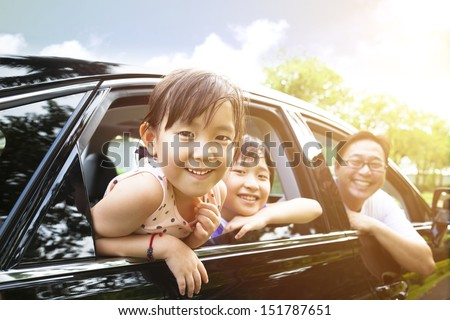 happy little girl with family sitting in the car  - stock photo