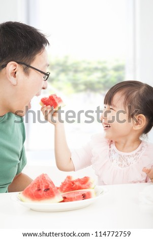 happy little girl with father eating fruits - stock photo
