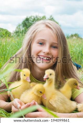 Happy little girl with goslings - stock photo