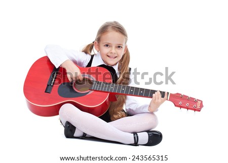 Happy little girl with guitar - sitting and playing, isolated - stock photo
