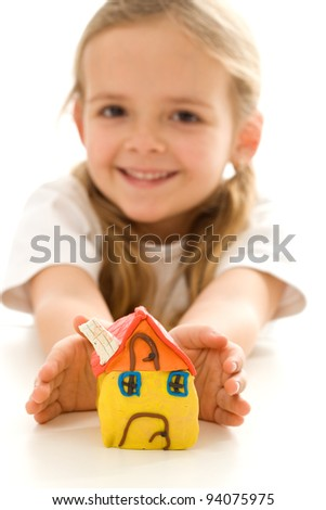 Happy little girl with hand made clay house - new home concept, isolated
