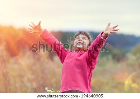 Happy little girl with hands up on the meadow in sunny day - stock photo