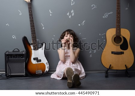 Happy little girl with harmonica in her hands produces nice melody. Positive emotions while playing music. Beautiful child sits on the floor near acoustic and bass guitars, special amp. - stock photo