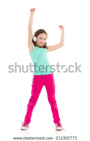Happy little girl with headphones listening to the music and dancing with arms raised. Full length studio shot isolated on white. - stock photo