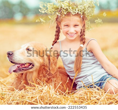 happy little girl with her dog golden retriever in rural areas in summer - stock photo