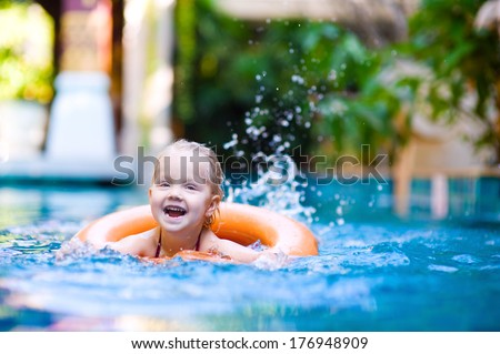 Happy little girl with lifebouy having fun in swimming pool - stock photo