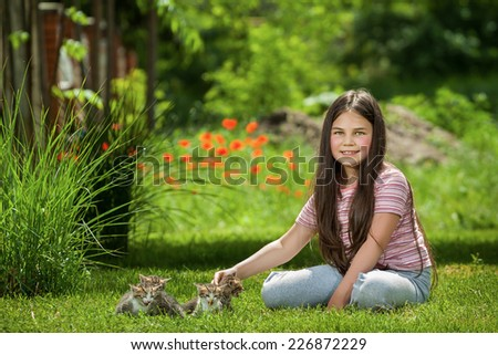 Happy little girl with little cats outdoor playing - stock photo