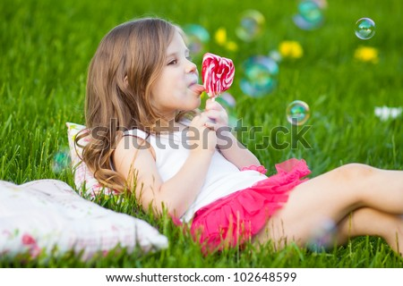 Happy little girl with lollipop resting on the grass in summer day - stock photo