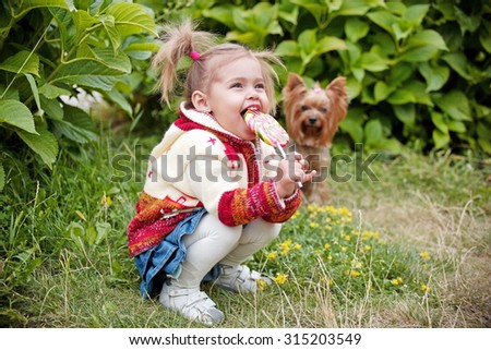 Happy little girl with lollipop resting on the grass in summer day