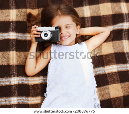 Happy little girl with old vintage retro camera having fun. Top view - stock photo