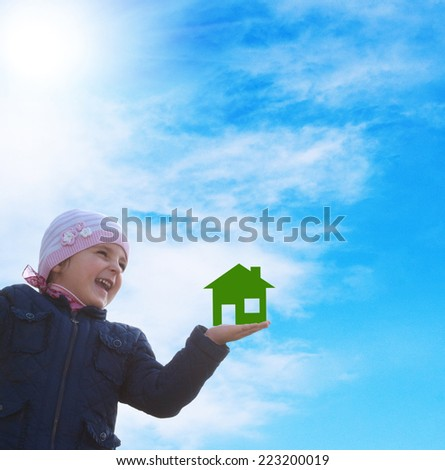 Happy little girl with paper green home on hand  on a sky blue background - stock photo
