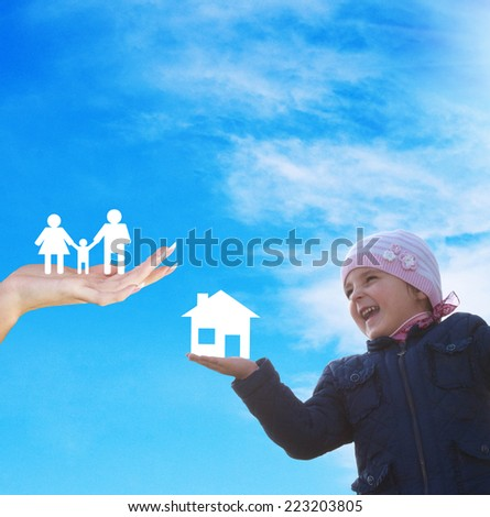 Happy little girl with paper house on hand.New home for family - stock photo