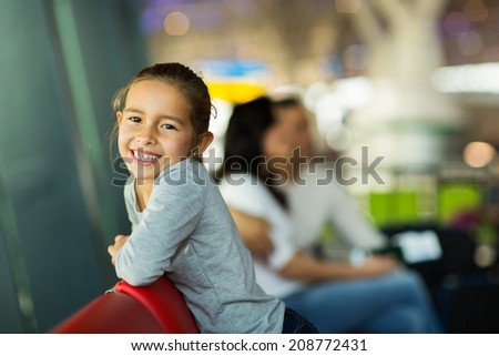 happy little girl with parents at airport waiting for flight  - stock photo